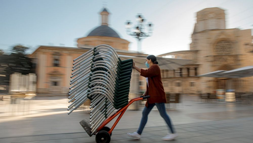 Una persona monta la terraza de un bar de una céntrica plaza de Valencia