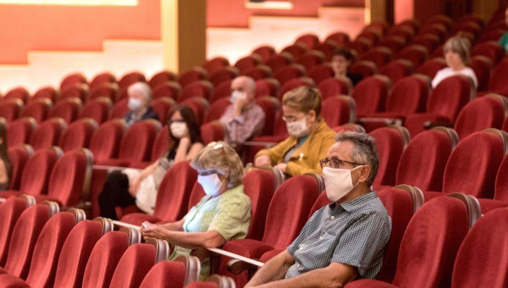 Varios espectadores y espectadoras esperan a que comience una sesión de cine en el verano de 2020