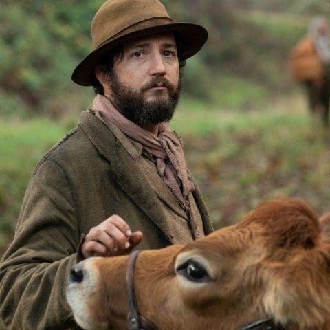 Imagen promocional de la película 'First cow', con el actor John Magaro y la vaca protagonista de la cinta