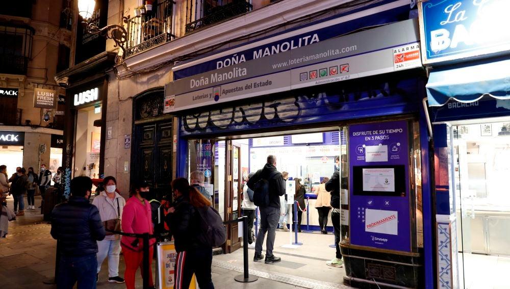 Varias personas esperan a las puertas de la administración de Lotería de Doña Manolita, en Madrid.