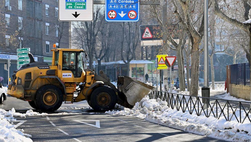 Una excavadora limpia de nieve una calle de Madrid