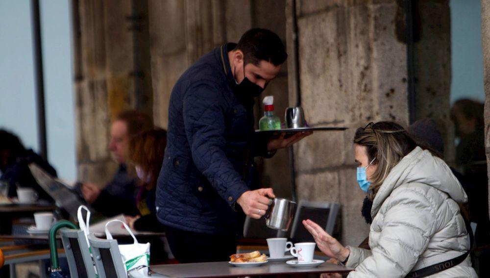 Una mujer toma un café en una terraza en Vigo