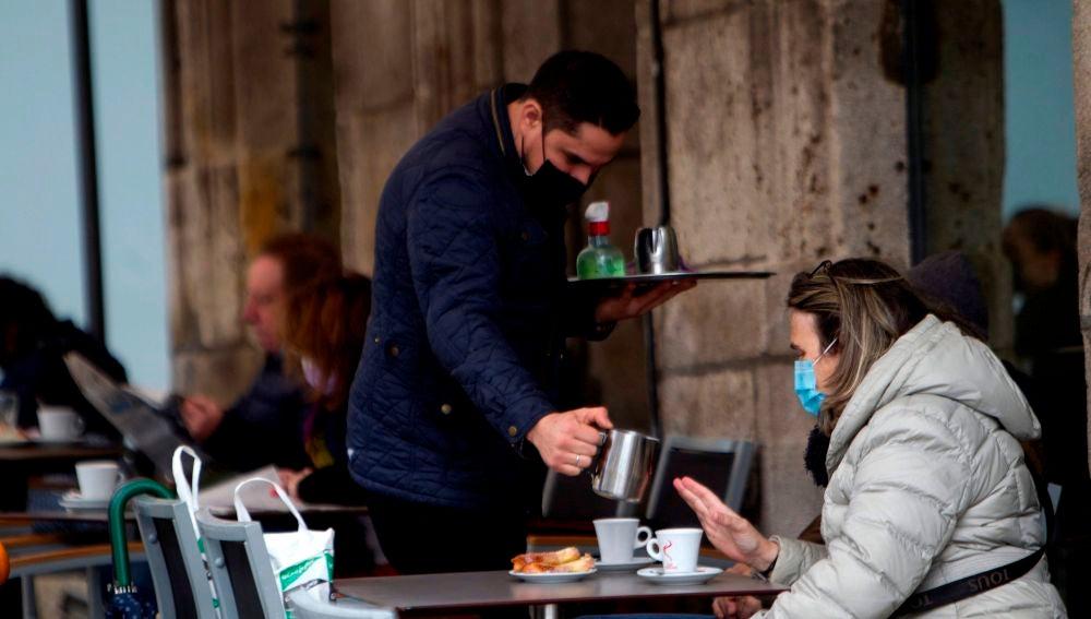 Un camarero sirve un café en la terraza de un bar en Vigo.