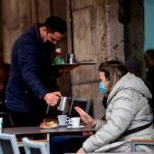Un camarero sirve un café en la terraza de un bar.