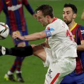 El centrocampista del Sevilla Ivan Rakitic (i) juega un balón ante Sergio Busquets, del FC Barcelona, durante el partido de ida de las semifinales de la Copa del Rey que disputan esta noche en el estadio Sánchez Pizjuán, en Sevilla.
