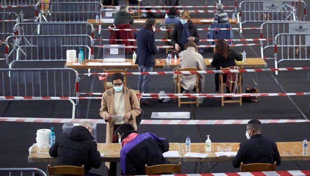 Varias personas votan en el colegio electoral del polideportivo municipal de Palau en Girona
