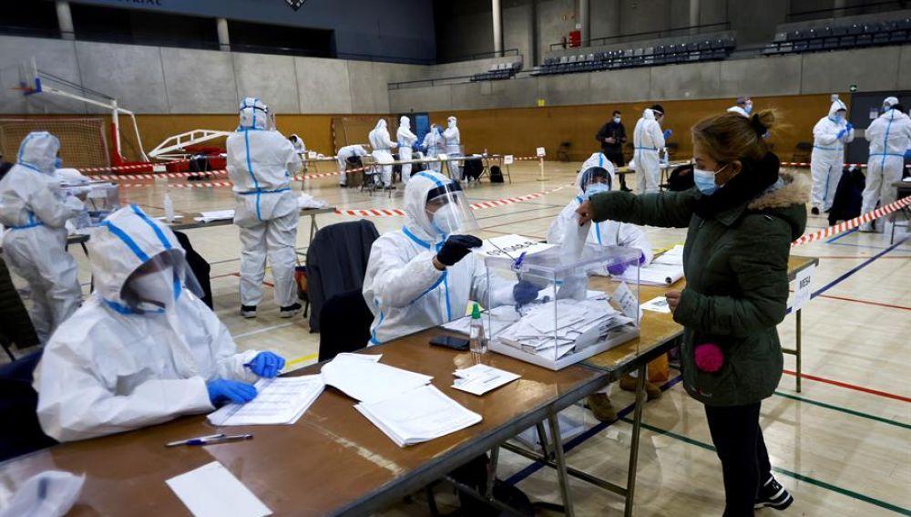 Varias personas equipadas con equipos de protección individual (EPI), trabajan en las mesas electorales del Polideportivo Municipal de la España Industrial de Barcelona
