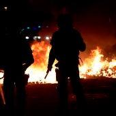 Agentes de los Mossos junto a una barricada en llamas