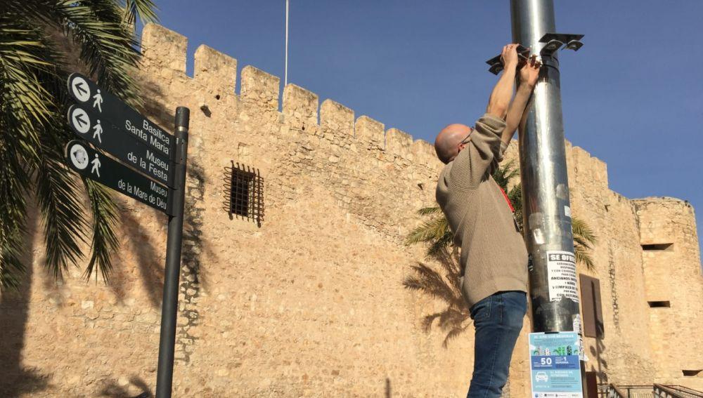 Investigador de la UMH coloca un captador en una farola junto al Palacio de Altamira de Elche.
