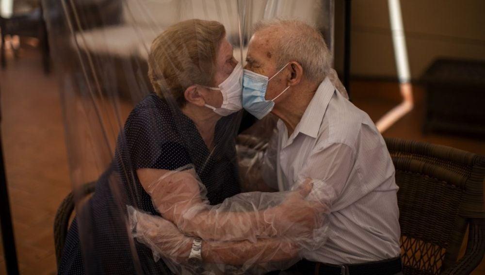 Una pareja de ancianos se besa con un plástico entre medias para evitar contagiarse.