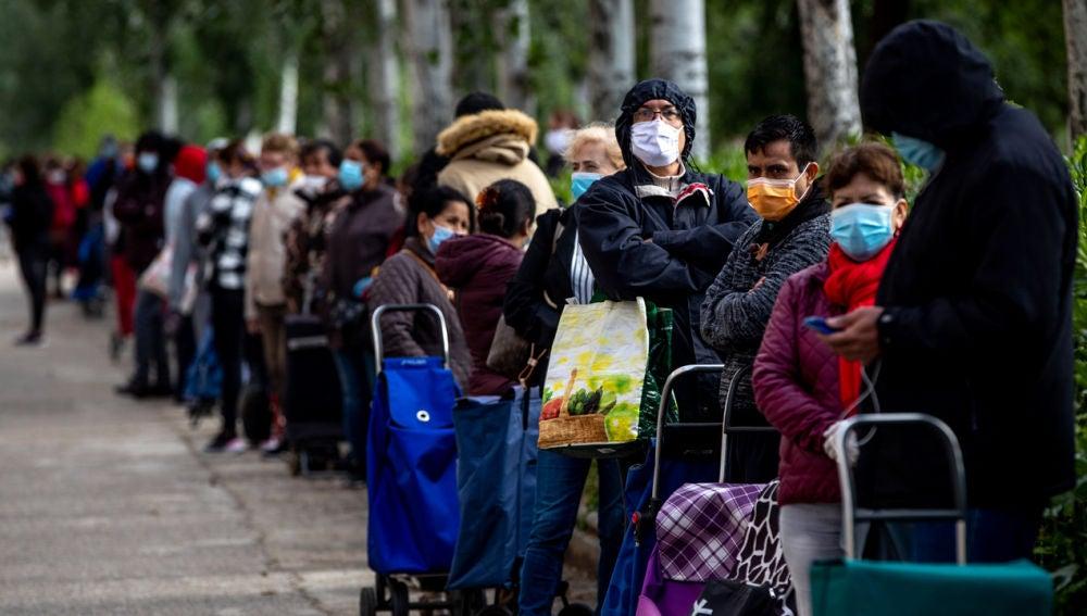 Personas haciendo cola para recoger comida en el barrio de Aluche de Madrid en mayo de 2020