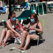 Dos mujeres con mascarillas en la playa de La Malagueta. En Málaga (Andalucía, España)
