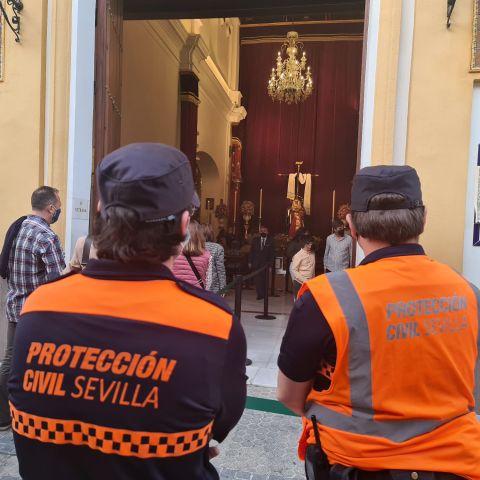 Agentes de protección civil controlan que se cumplan las medidas ante las puertas de una iglesia de Sevilla