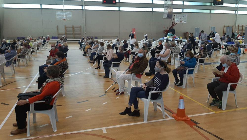 Ciudadanos en la zona post-vacunación del pabellón deportivo El Toscar de Elche.