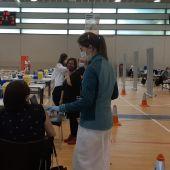 Una sanitaria vacuna a una ciudadana en el pabellón deportivo El Toscar de Elche.
