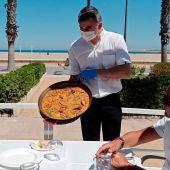 Un camarero sirviendo una paella en un restaurante valenciano