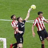 El portero del Athletic de Bilbao Unai Simón despeja un balón junto al delantero del Deportivo Alavés Joselu