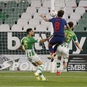 El centrocampista del Atlético de Madrid Saúl Ñíguez salta por el balón con Álex Moreno, del Real Betis