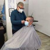 Mario Andrés atiende a un cliente habitual, José Rodríguez, en su peluquería de la calle Capità Vilà de Palma