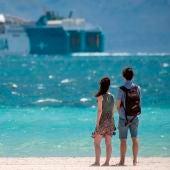 Una pareja pasea por la playa.