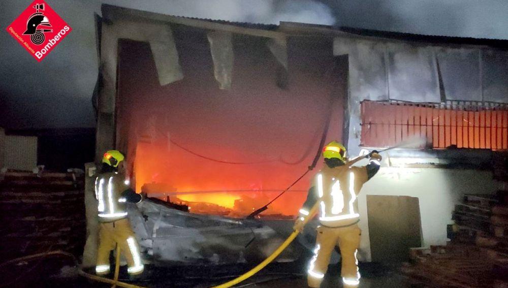 Bomberos en las labores de extinción del incendio de la fábrica de palets de Elche.