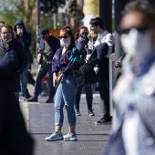 Gente caminando por la calle con mascarillas.