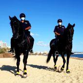 Agentes de la unidad de la policía montada de Palma patrullan las playas de la ciudad durante la revetla de Sant Joan.