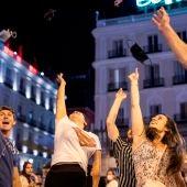 Varios madrileños lanzan las mascarillas al aire después de la entrada en vigor de su exención en el exterior.