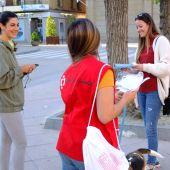 Voluntarios de Cruz Roja repartiendo mascarillas en la plaza de Navarra