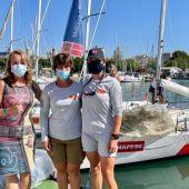 Las regatistas Aina Bauzà y Leah Sweet posan junto a su barco, acompañadas de Elka Dimitrova