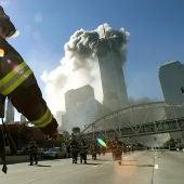 Los bomberos caminan hacia una de las torres antes del colapso tras el impacto de un avión el 11S