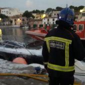 Un bombero frente a la embarcación incendiada en Portopetro, que ha obligado a activar el plan anticontaminación