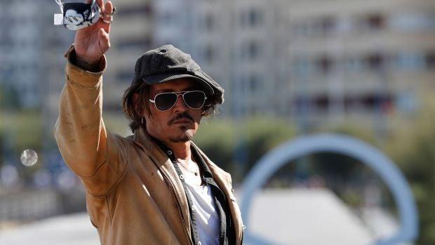 Johnny Depp saluda a los fotógrafos en el photocall del Festival de San Sebastián 2021