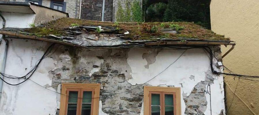 Parte de un tejado se desploma en Luarca sobre la acera y la calzada.
