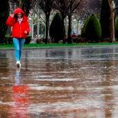 Una mujer se protege de la lluvia, en una fotografía de archivo
