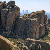 Vista genérica de la Pedriza con las cuatro torres de Madrid al fondo
