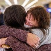 Una madre y una hija se abrazan en la terminal de un aeropuerto